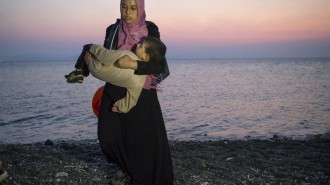 A Syrian migrant woman carries her child away upon their arrival by a dinghy at the southeastern Greek island of Kos, Greece, early Thursday, Aug. 20, 2015. Greece this year has been overwhelmed by record numbers of migrants arriving on its eastern Aegean islands, with more than 160,000 landing so far.  (AP Photo/Alexander Zemlianichenko)